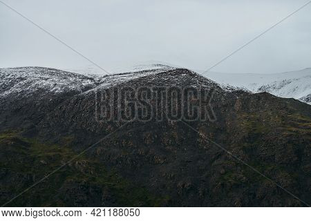 Minimalist Highlands Landscape With Snow-capped Mountains Under Cloudy Sky. Snowbound High Mountain