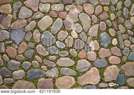 The Surface Of The Sidewalk Lined With Untreated Cobblestone. View From Above. Close Up.