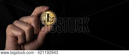 Litecoin Golden Coin In Male Hand Over Black Background. Banner With Space For Text.