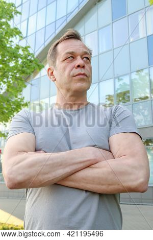 Street Portrait Of A Strong Physique Man Of 40-50 Years Old In A Gray T-shirt Against The Background