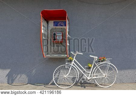 Public Telephone And White Bicycle With Flowers Decor