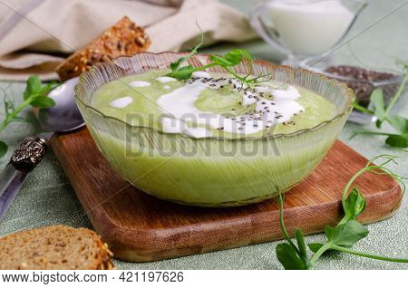 Thick Cream Soup Of Green Vegetables With White Sauce, Chia Seeds And Pea Sprouts On A Green Backgro