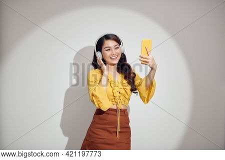 Enjoy Listening To Music. Beautiful Young Woman With Headphones Listening Music And Making Selfie