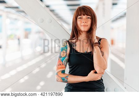 Portrait Of Young Pretty Woman With Tattoos On Her Arm, Posing, Standing Near A White Staircase. In