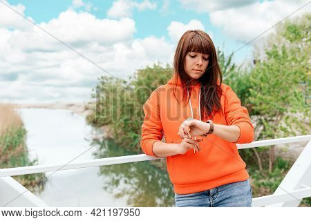 A Young Waiting Caucasian Woman Looks At Her Wristwatch. Park And River On The Background. The Conce