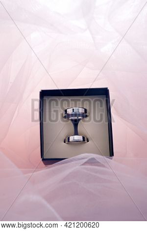 Platinum wedding rings on a pink dress background