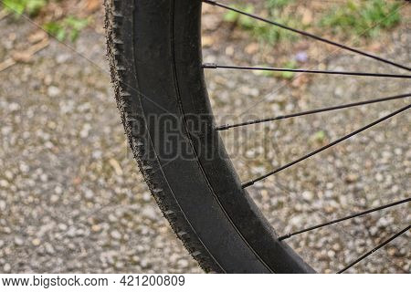 Part Of A Wheel Made Of Black Rubber Tire And Gray Metal Spokes On A Gray Background