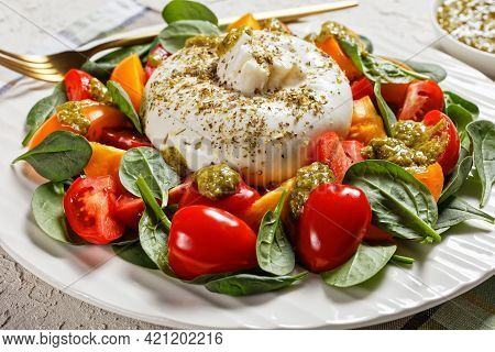 Close-up Of Spinach, Tomato And Burrata Cheese Salad With Basil Pesto Dressing On A White Plate, Ita