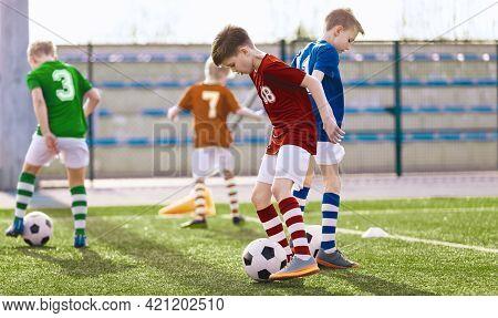 Group Of Children Running Soccer Balls On Training Grass Field. Soccer Stadium In The Background. Fo