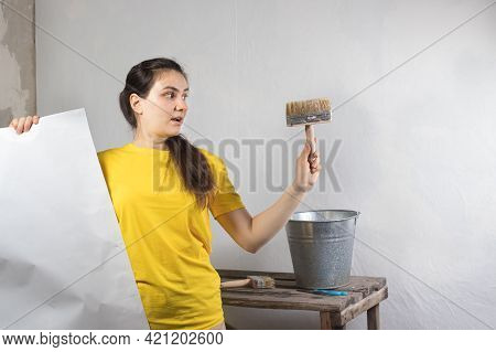 A Woman Repairman Glues White Wallpaper On The Wall. Repair Work, Wallpapering. Place For Text Copy