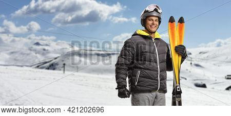 Man holding skiing equipment on a snowy mountain slopes and smiling at camera