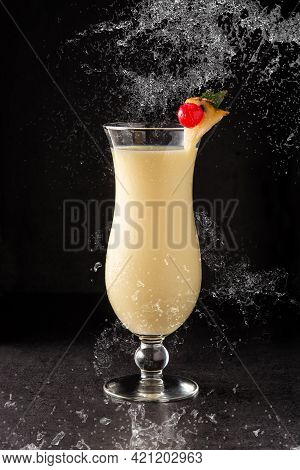 Splash Of Pina Colada Cocktail Decorated With A Piece Of Pineapple And Cherry On Black Background