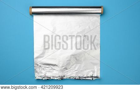 Unwrapped Roll Of Gray Foil On A Blue Background, Top View