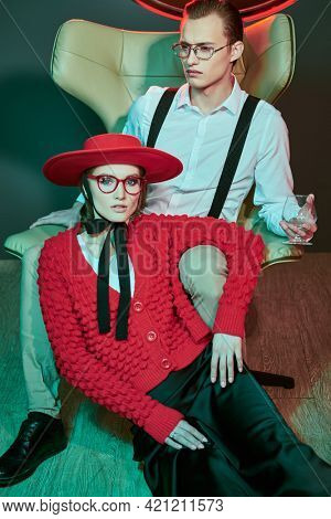 Handsome young man sits on a leather armchair with a beautiful young woman. Luxury apartment, dating. Glamorous lifestyle. Fashion shot.