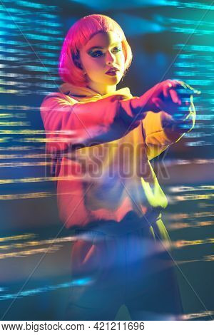 Youth fashion and beauty trends.  Modern girl with bright pink hair and glitter makeup poses in yellow suit in mixed color light. Sport chic fashion.