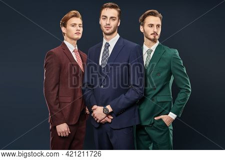 Men's fashion. Three handsome men in elegant suits posing together on a dark blue background. Male beauty. Studio portrait.