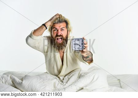Sleepy Mad Guy And Alarm Clock In Bed. Bearded Man With Alarm Clock. Sleep Disorder. Awakening Conce