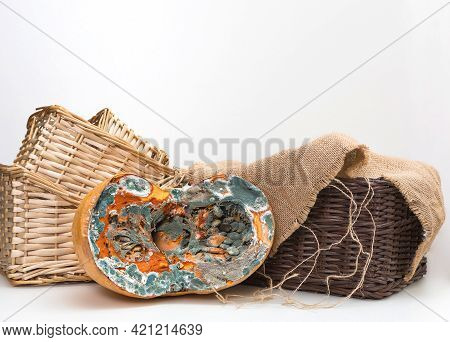Orange Moldy Cut Of A Pumpkin Against The Background Of Light And Dark Baskets And Burlap On   White