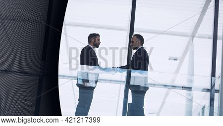 Technology background over two businessmen shaking hands at modern office. global business and technology concept