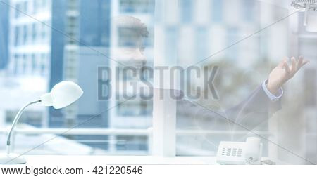 Composition of businessman talking in office over modern office building. global business and finance concept digitally generated image.