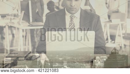 Composition of businessman using laptop in office over cityscape. global business and finance concept digitally generated image.