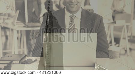 Composition of smiling businessman using laptop over modern office building. global business and finance concept digitally generated image.