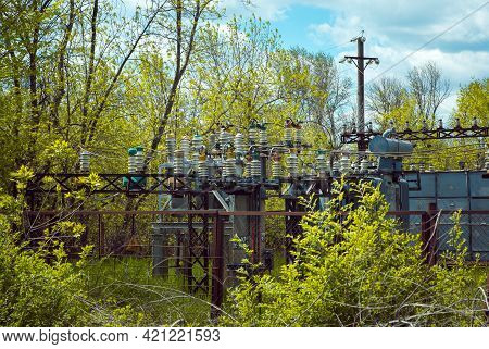 High Voltage Power Transformer Substation. Object On The Background Of Green Trees.