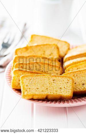 Sliced sponge dessert. Sweet sponge cake on white kitchen table.