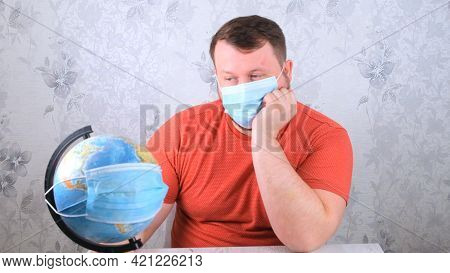 Male Is Looking At The Globe In A Protective Mask And A Pandemic Vaccine. Corona Virus Treatment Con