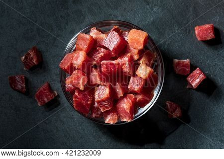 Iberian Ham (serrano) Cut Into Cubes (diced). In A Glass Bowl. Black Textured Background.