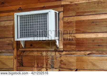 Horizontal Shot Of A Window Air Conditioner Unit In The Outer Wall Of A Retail Building.
