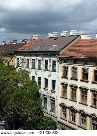 A Street With Tenements And A Sky With Thunder Clouds.