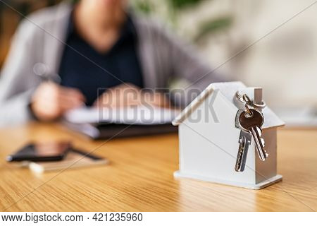 Real estate agent signing contract to rent or sell a property. Close up of scale model of a house with keys on table. White cardboard model house with keys hanging on chimney on desk.