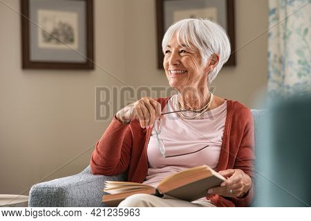 Senior woman holding eyeglasses thinking while relaxing at home. Happy elderly woman reading book sitting on couch. Beautiful old teacher takes a break from reading while looking through the window.