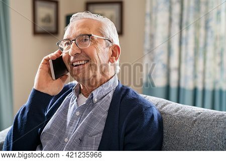 Smiling old man talking over smartphone while relaxing at home. Senior man after retirement using smart phone to connect with friends and family. Carefree elder talking over phone with her daughter.