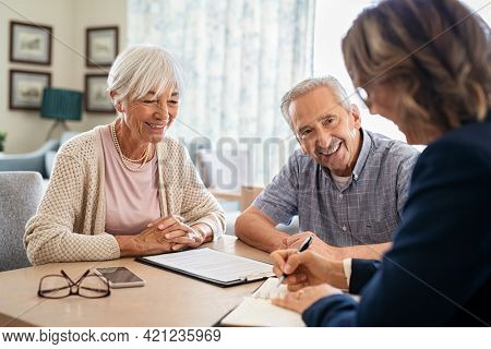 Senior couple planning their investments with financial advisor at home. Happy aged couple planning their medical insurance with advisor. Old couple consulting with insurance agent.