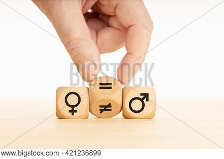 Gender Equality Concept. Hand Turns A Wooden Block And Changes A Unequal Sign To A Equal Sign Betwee