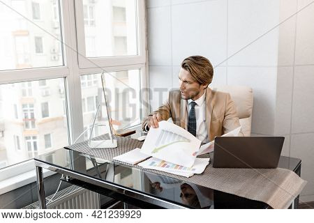 Portrait Of Young Attractive Business Man, Adjusting His Tie, Stand In His Office After Online Meeti