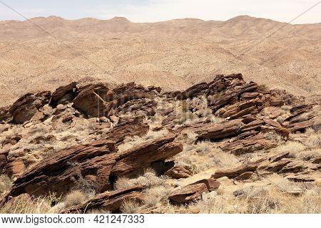 Rocks And Boulders On Arid Badlands With Barren Mountains Beyond Taken At The Rural Colorado Desert