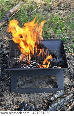 Coals Are Burning In The Grill. Preparing For A Picnic. Brazier With Burning Coals In A Forest Glade