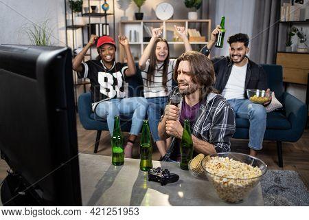 Group Of Four Multicultural People Singing Karaoke, Drinking Beer And Eating Snacks During Happy Wee
