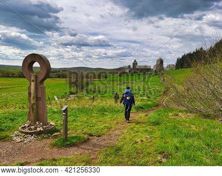 Pilgrim Arriving In Aubrac, French Part Of The Camino De Santiago. Way Of Saint James.