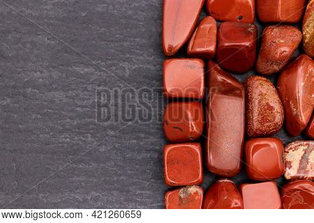 Red Jasper Heap Jewel Stones Texture On Half Black Stone Background. Place For Text.