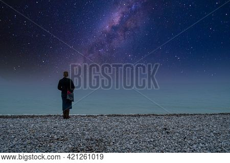 Milky Way With Silhouette Of A Woman. Landscape With Night Starry Sky. Standing Woman On The Beach A