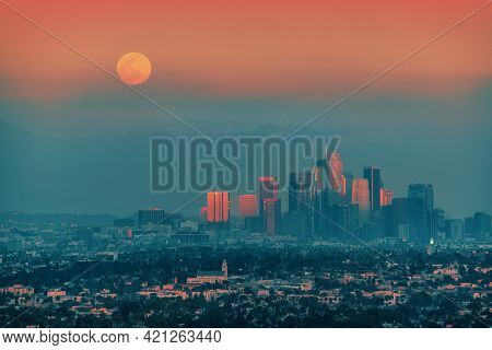 Full moon rising above downtown Los Angeles skyline background.