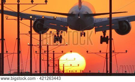 Jumbo jet plane landing in airport at sunset, flying into sun.