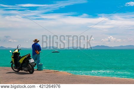 Koh Larn Island. A Man Is Fishing In The Sea At Koh Lan Amid The Clear Sky And Emerald Green Water.
