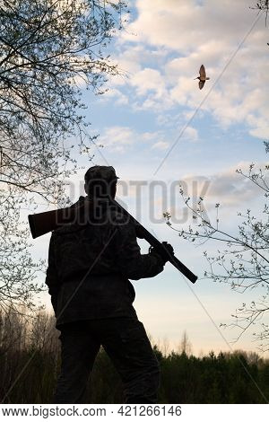 A Hunter With An Unloaded Rifle On His Shoulder Stands In The Twilight In A Forest Clearing. He Look