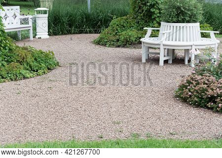 Landscaping Of The Local Area With White Benches, Gravel Paths And Flower Beds