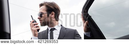 Side View Of Bearded Bodyguard In Suit And Sunglasses Using Walkie Talkie Near Modern Car, Banner.